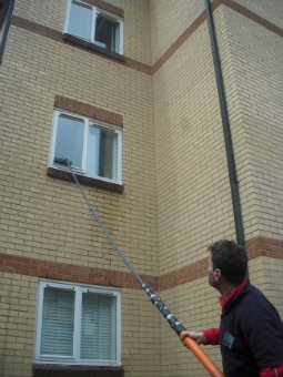 cleaning high windows with water-fed long pole